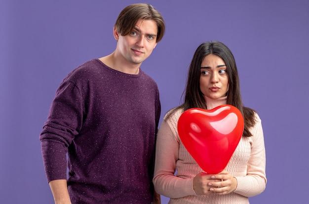 Ontevreden jong koppel op valentijnsdag meisje met hart ballon geïsoleerd op blauwe achtergrond