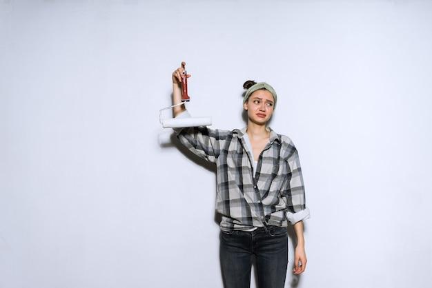 Ontevreden jong meisje in shirt moe van reparaties, houdt roller vast om muren te schilderen