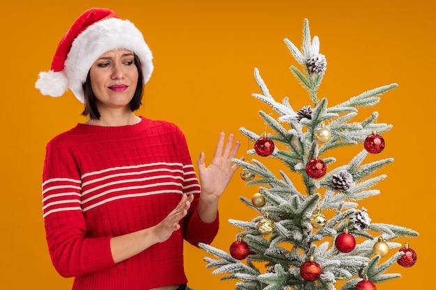Ontevreden jong meisje met kerstmuts staande in de buurt van versierde kerstboom kijken naar het weigeren gebaar geïsoleerd op oranje muur
