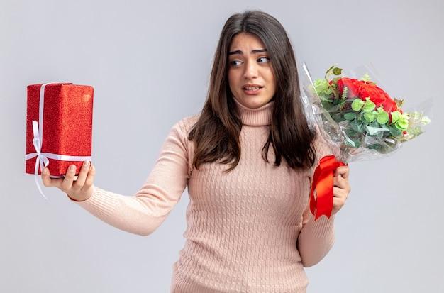 Ontevreden jong meisje op valentijnsdag met boeket kijken naar geschenkdoos in haar hand geïsoleerd op een witte achtergrond