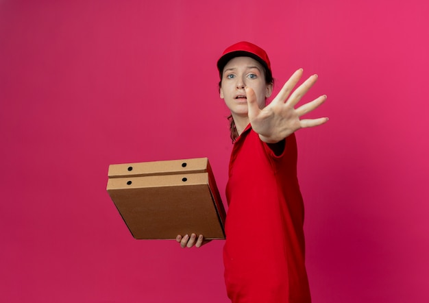 Ontevreden jong mooi bezorgmeisje in rood uniform en pet die in profielweergave staat met pizzapakketten en hand uitstrekkend en nee gebarend