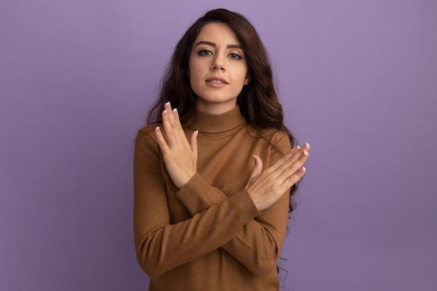 Ontevreden jong mooi meisje dat bruine coltrui draagt die gebaar van geen toont dat op purpere muur wordt geïsoleerd