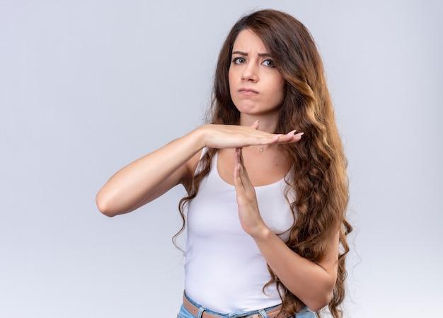 Ontevreden jong mooi meisje dat time-outgebaar op geïsoleerde witte muur doet