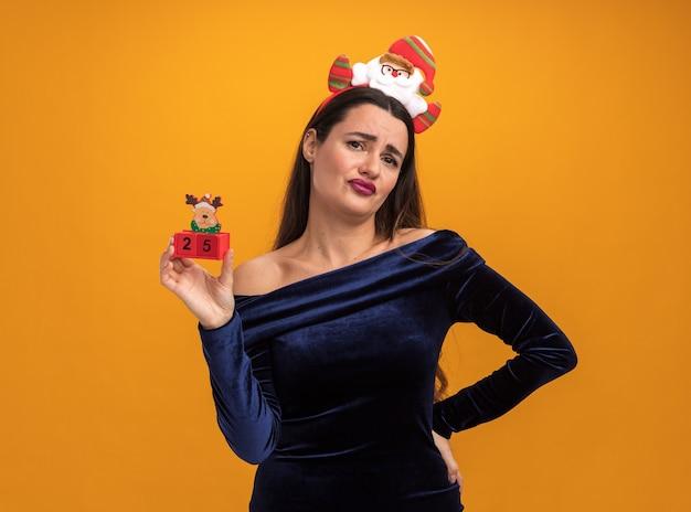 Ontevreden jong mooi meisje draagt blauwe jurk en kerst haar hoepel bedrijf speelgoed hand zetten heup geïsoleerd op een oranje achtergrond