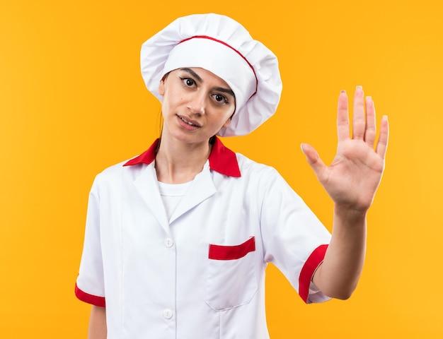 Ontevreden jong mooi meisje in chef-kok uniform weergegeven: stop gebaar