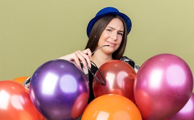Ontevreden jong mooi meisje met een blauwe hoed die achter ballonnen staat en een bril vasthoudt die op een olijfgroene muur is geïsoleerd