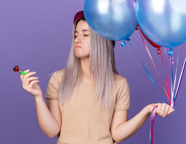 Ontevreden jong mooi meisje met een feesthoed die ballonnen vasthoudt en naar een feestfluitje in haar hand kijkt, geïsoleerd op een blauwe muur