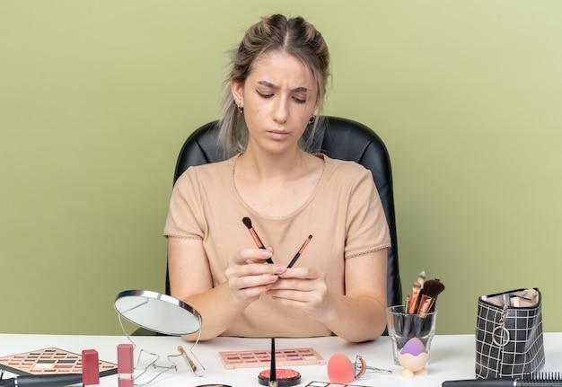 Ontevreden jong mooi meisje zit aan bureau met make-up tools houden en kijken naar make-up borstels geïsoleerd op olijf groene achtergrond