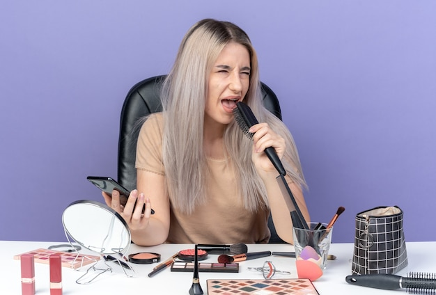 Ontevreden jong mooi meisje zit aan tafel met make-up tools met kam met telefoon geïsoleerd op blauwe achtergrond
