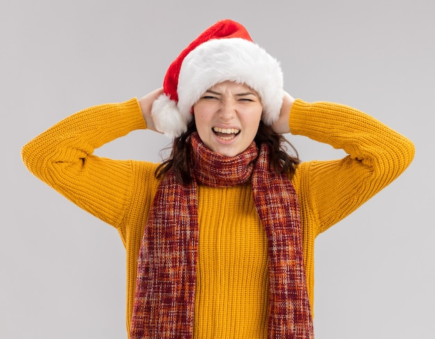 Ontevreden jong slavisch meisje met kerstmuts en met sjaal om nek houdt hoofd geïsoleerd op een witte achtergrond met kopie ruimte