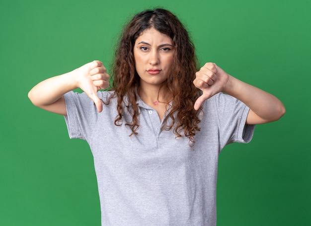 Ontevreden jong vrij kaukasisch meisje dat duimen naar beneden laat zien