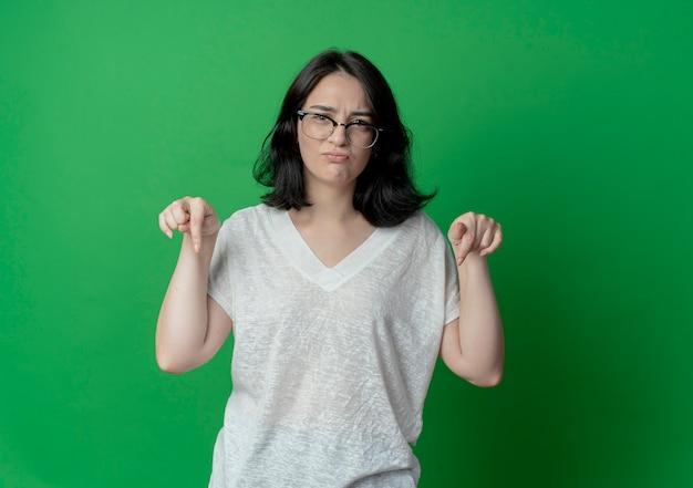 Ontevreden jong vrij kaukasisch meisje dat glazen draagt die naar beneden wijzen geïsoleerd op groene achtergrond met exemplaarruimte