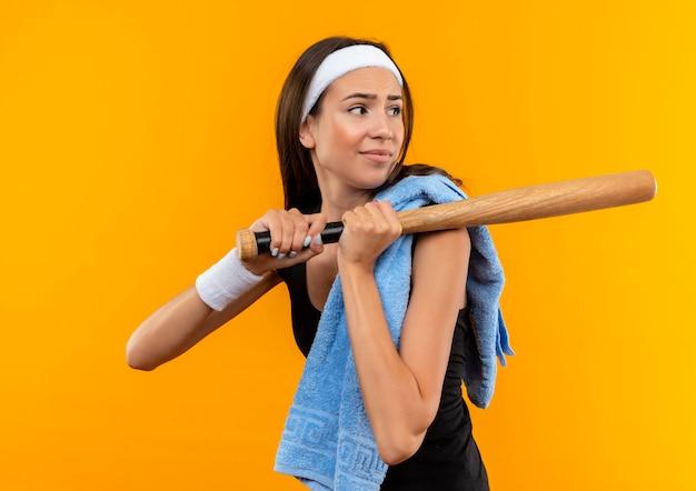 Ontevreden jong vrij sportief meisje hoofdband en polsbandje met handdoek op haar schouder houden honkbalknuppel en kijken naar kant geïsoleerd op oranje ruimte