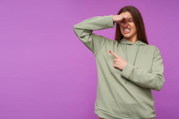 Ontevreden jonge aantrekkelijke langharige brunette vrouw grimassen haar gezicht en neus sluiten met opgeheven hand terwijl ze probeert om slechte geur te vermijden, geïsoleerd over paarse muur