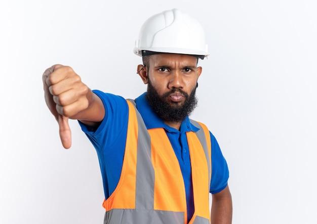 Ontevreden jonge afro-amerikaanse bouwer man in uniform met veiligheidshelm duim omlaag geïsoleerd op een witte achtergrond met kopie ruimte copy