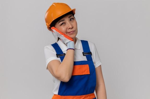 Ontevreden jonge aziatische bouwvrouw met oranje veiligheidshelm en handschoenen die de hand op haar gezicht legt en naar de zijkant kijkt