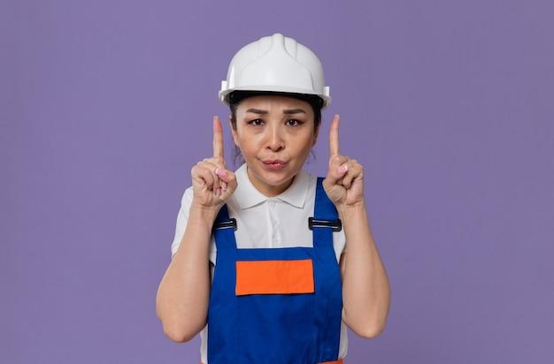 Ontevreden jonge aziatische bouwvrouw met witte veiligheidshelm die naar boven wijst