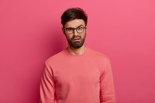 Ontevreden jonge bebaarde man walgt van ontevreden uitdrukking, reageert op iets onaangenaams, fronst gezicht, draagt bril en trui, staat binnen tegen roze muur. emoties concept