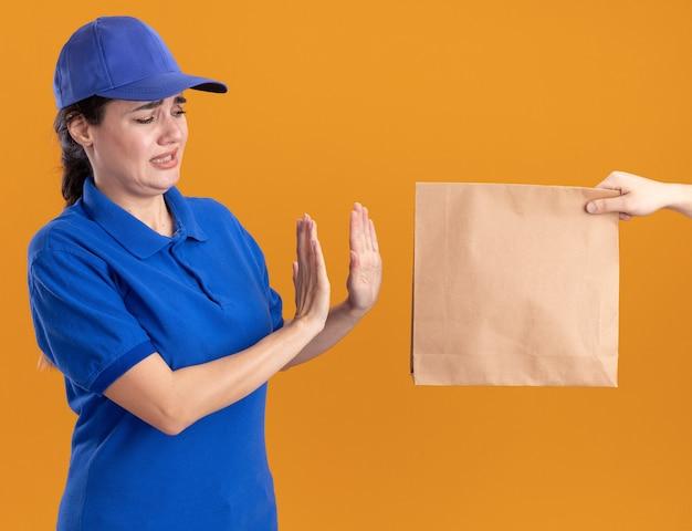 Ontevreden jonge bezorger in uniform en pet in profielweergave iemand die een papieren pakket naar haar uitrekt, ze kijkt naar een pakket dat een weigeringsgebaar doet geïsoleerd op een oranje muur