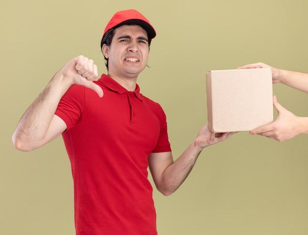 Ontevreden jonge blanke bezorger in rood uniform en dop die kaartdoos geeft aan klant met duim omlaag