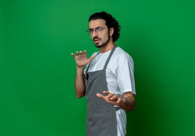 Ontevreden jonge blanke mannelijke kapper bril en golvende haarband in uniform strekken hand op camera gebaren niet geïsoleerd op groene achtergrond met kopie ruimte