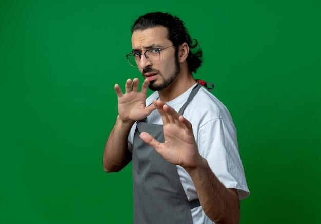 Ontevreden jonge blanke mannelijke kapper dragen van uniform en bril permanent in profiel te bekijken hand uitrekken op camera en houden een ander in de lucht geïsoleerd op groene achtergrond met kopie ruimte