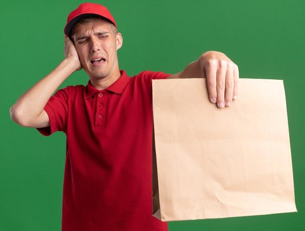 Ontevreden jonge blonde bezorger legt hand op gezicht en kijkt naar papieren pakket