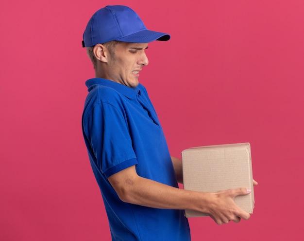 Ontevreden jonge blonde bezorger staat zijwaarts met zware kartonnen doos