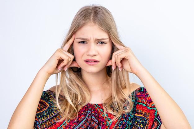 Ontevreden jonge blonde vrouw die handen op haar hoofd legt en kijkt