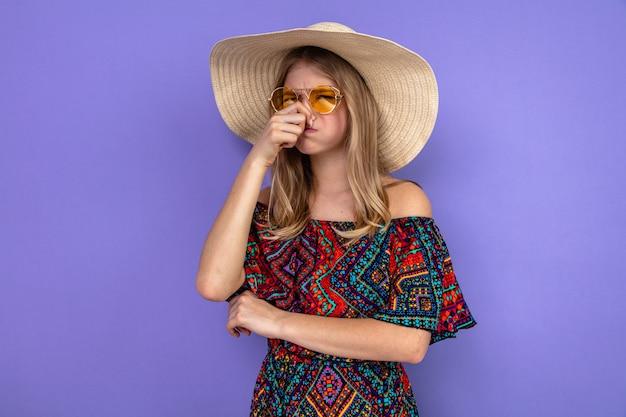 Ontevreden jonge blonde vrouw met zonnebril en met zonnehoed die haar neus vasthoudt