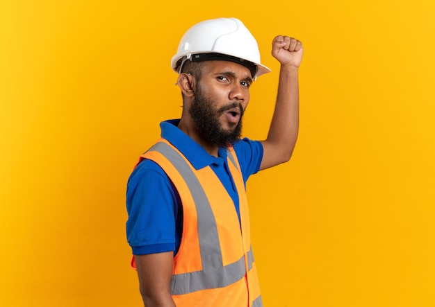 Ontevreden jonge bouwer man in uniform met veiligheidshelm die zijn vuist opheft geïsoleerd op oranje muur met kopieerruimte