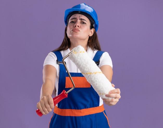 Ontevreden jonge bouwersvrouw in eenvormig standhouden rolborstel die op purpere muur wordt geïsoleerd