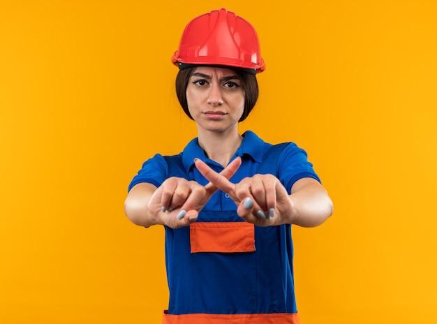 Ontevreden jonge bouwersvrouw in uniform die gebaar van nee toont