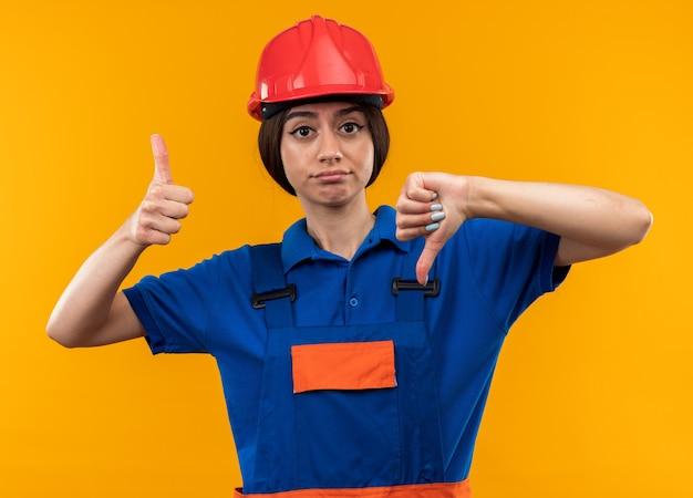 Ontevreden jonge bouwvrouw in uniform met duimen naar beneden en omhoog