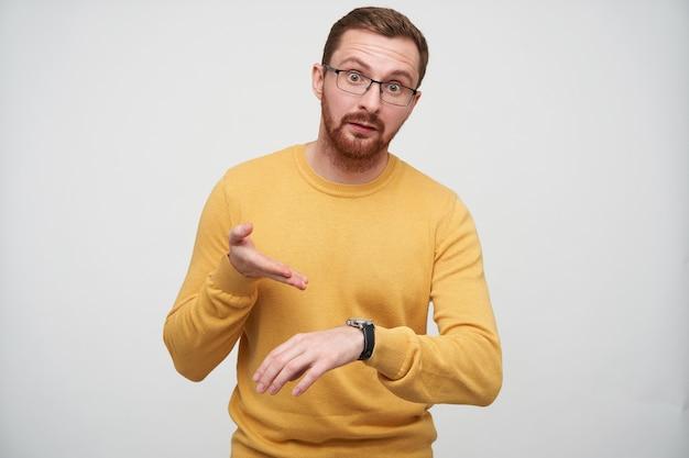 Ontevreden jonge bruinharige bebaarde man in brillen wijzend verontwaardigd op zijn horloge met polsbandje, ontevreden dat iemand te laat is, geïsoleerd