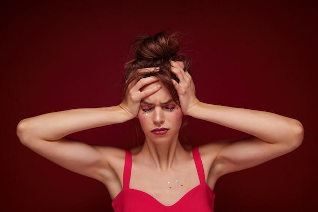 Ontevreden jonge bruinharige vrouw met knot kapsel draagt roze top met bandjes tijdens het poseren, fronsend gezicht en haar hoofd geklemd, met hoofdpijn na feest