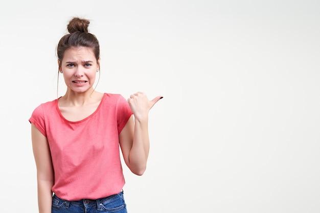 Ontevreden jonge bruinharige vrouw met natuurlijke make-up grimassen haar gezicht terwijl duimend opzij, staande op witte achtergrond in fundamentele roze t-shirt