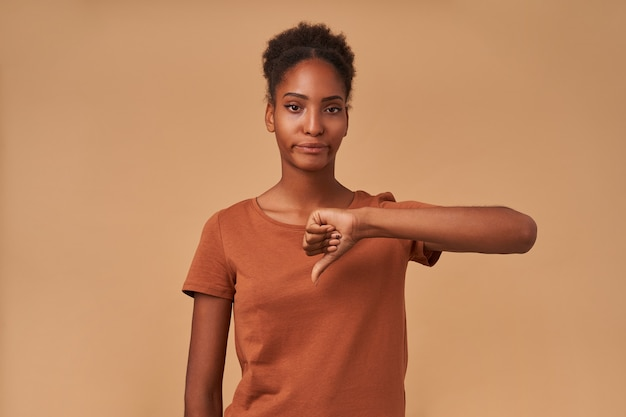 Ontevreden jonge bruinogige krullende brunette vrouw met donkere huid die de hand omhoog houdt terwijl ze naar beneden duimen met steenbolk, staande op beige