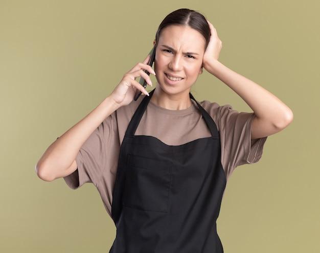 Ontevreden jonge brunette kapper meisje in uniform legt hand op het hoofd en praat over telefoon op olijfgroen