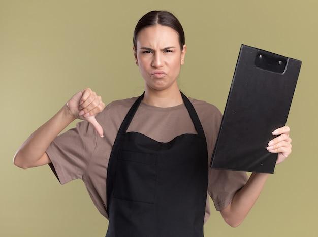 Ontevreden jonge brunette kappersmeisje in uniform duimen naar beneden en houdt klembord geïsoleerd op olijfgroene muur met kopieerruimte