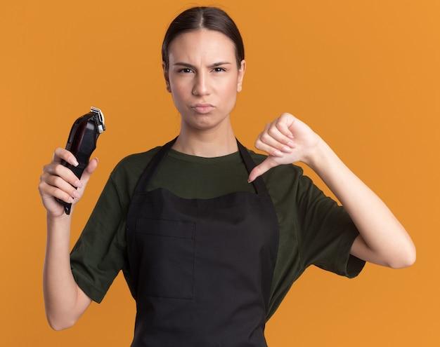 Ontevreden jonge brunette kappersmeisje in uniform duimen naar beneden en houdt tondeuses geïsoleerd op oranje muur met kopieerruimte