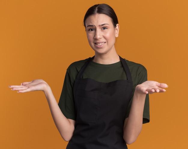 Ontevreden jonge brunette kappersmeisje in uniform houdt handen open geïsoleerd op oranje muur met kopieerruimte