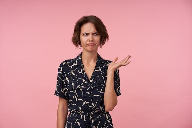 Ontevreden jonge brunette vrouw met kort kapsel staande en opgeheven handpalm ontevreden, fronsende wenkbrauwen met gevouwen lippen terwijl ze opzij kijkt