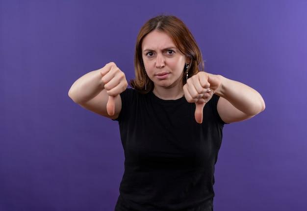 Ontevreden jonge casual vrouw die naar beneden wijst op geïsoleerde paarse muur