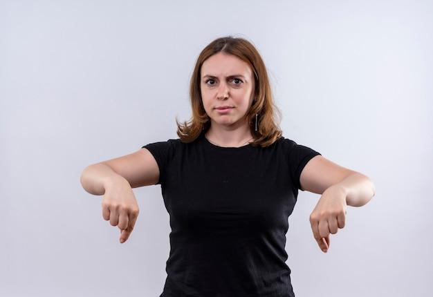 Ontevreden jonge casual vrouw die naar beneden wijst op geïsoleerde witte muur
