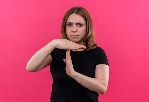 Ontevreden jonge casual vrouw gebaren time-out op geïsoleerde roze muur met kopie ruimte