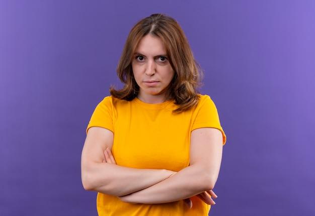 Ontevreden jonge casual vrouw stond met gesloten houding op geïsoleerde paarse muur met kopie ruimte