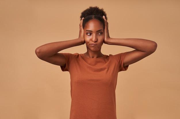 Ontevreden jonge donkere gekrulde vrouw die haar mond en kegelvormige oren met opgeheven handpalmen draait, vrijetijdskleding draagt terwijl ze op beige staat