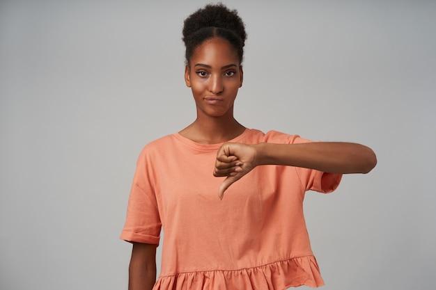 Ontevreden jonge donkere gekrulde vrouw met casual make-up die hand omhoog houdt terwijl ze een hekel aan teken toont, staande op grijs in roze t-shirt