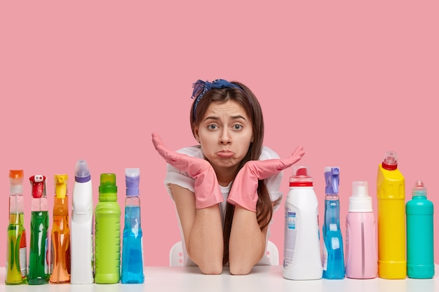 Ontevreden jonge huishoudster portemonnees lippen heeft droevige uitdrukking, kijkt met een ongelukkig gezicht, spreidt handen